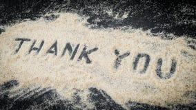 Word Thank You written on white sand