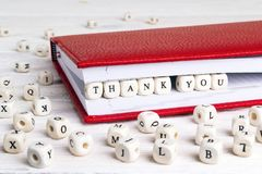 Word Thank you written in wooden blocks in red notebook on white stock images