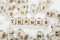 Thanks word written on wood block. Word THANKS formed by wood alphabet blocks. On old wooden table Royalty Free Stock Images