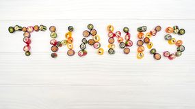 A word THANKS made of colored caramel candies. On wooden white table. Copy space. Top view Royalty Free Stock Photography