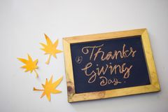 The word Thanksgiving written by hand on a blackboard in white/grey background.  royalty free stock photos