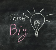 The word think big and light bulb. Drawn on a chalk board,business concept stock image