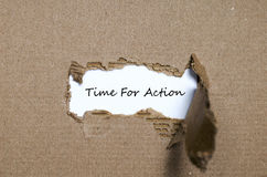 The word time for action appearing behind torn paper Stock Photo
