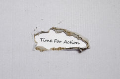 The word time for action appearing behind torn paper Stock Images