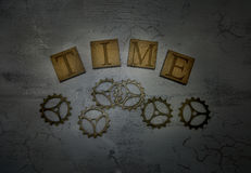 Word time and cogs. Wooden letters with word time and cogs on dark background Stock Photos