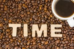 Word Time composed of large letters with wooden structure is located on the background of coffee beans with a cup of brewed coffee Royalty Free Stock Photography