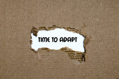 The word time to adapt appearing behind torn paper. The word time to adapt Stock Image