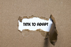 The word time to adapt appearing behind torn paper. The word time to adapt Stock Images