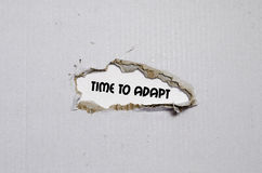 The word time to adapt appearing behind torn paper. The word time to adapt Royalty Free Stock Photos