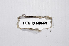 The word time to adapt appearing behind torn paper. The word time to adapt Stock Photography