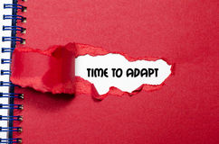 The word time to adapt appearing behind torn paper. The word time to adapt Stock Photos