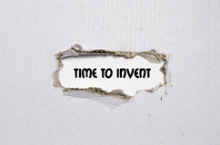 The word time to invent appearing behind torn paper Stock Photography