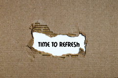 The word time to refresh appearing behind torn paper Stock Photos