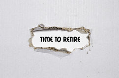 The word time to retire. Appearing behind torn paper Royalty Free Stock Photography