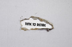 The word time to retire appearing behind torn paper. The word time to retire Royalty Free Stock Photos