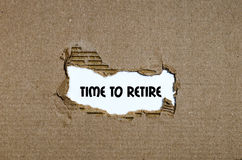 The word time to retire appearing behind torn paper Stock Photos