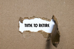 The word time to retire appearing behind torn paper. The word time to retire behind torn paper Royalty Free Stock Images