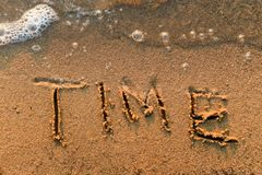 Word Time written in the sand. At the beach with bubbles waves. Background Stock Photo