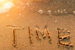 Word Time written in the sand. At the beach with bubbles waves at sunset. Symbol of outgoing time Royalty Free Stock Photography