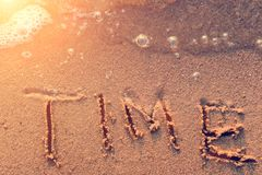 Word Time written in the sand. At the beach with bubbles waves at sunset, toned Stock Photo
