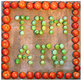 Word tomato written with green and red tomatoes on wooden backgr Stock Photography