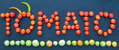 Word tomato written with green and red tomatoes on wooden board Royalty Free Stock Photography