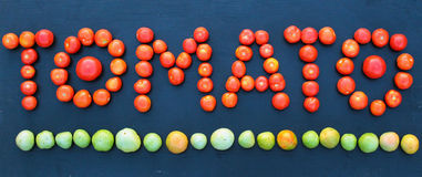 Word tomato written with green and red tomatoes on wooden board Royalty Free Stock Images