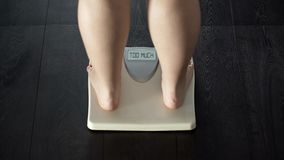 Word too much written on scales screen, woman warned about excessive weight. Stock photo royalty free stock photos