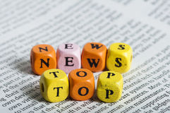 Word top news.Wooden cubes on magazine Royalty Free Stock Photo