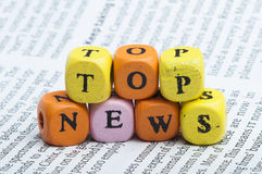 Word top news.Wooden cubes on magazine Royalty Free Stock Images