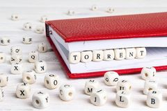 Free Word Torrent Written In Wooden Blocks In Red Notebook On White W Stock Photos - 118395913