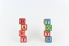 The Word Toy and Baby in Wooden Childrens Blocks. Baby Toys - Isolated Text Word In Wooden Childrens Building Blocks with a White Background. The blocks are Royalty Free Stock Photos