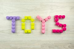 The word toys spelled on a wooden background royalty free stock image