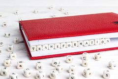 Word Transformation written in wooden blocks in red notebook on. White wooden table. Wooden abc Royalty Free Stock Photography
