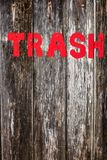 The word `trash` painted in red on a rustic wooden background Stock Photo