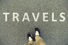 Word travels written on an asphalt road. Top view of the legs an. D shoes. POV Royalty Free Stock Image