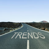 Word trends in a lonely road. The word trends written in the asphalt of a lonely road with no traffic in a rural landscape royalty free stock images