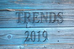 The word trends and number 2019 on a wooden blue surface. royalty free stock photography