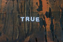 The word true written in white block letters. On a orange and brown wood surface Stock Images
