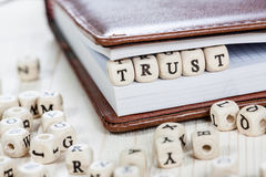 Word TRUST on old wooden table. Stock Images