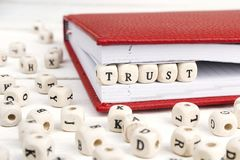 Word Trust written in wooden blocks in red notebook on white woo. Den table. Wooden abc Stock Images