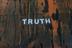 The word truth written in white block letters. On a orange and brown wood surface Stock Image