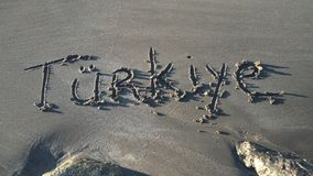 Word Turkey written in sand in Turkish. Top view stock video footage