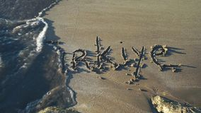 Word Turkey written in sand in Turkish. Washed away by wave. Slow motion stock footage