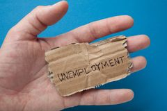 The word `unemployment` on the torn old cardboard in the hand of a man. stock photos