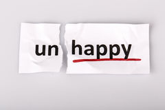 The word unhappy changed to happy on torn paper Stock Image