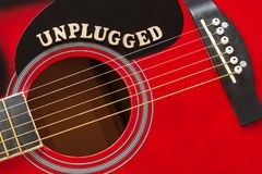 Word Unplugged with wooden letters, closeup on a surface of red acoustic guitar. Music entertainment background.  stock photo