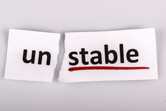 The word unstable changed to stable on torn paper Stock Images