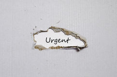 The word urgent appearing behind torn paper Royalty Free Stock Photography