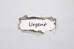 The word urgent appearing behind torn paper Stock Photo